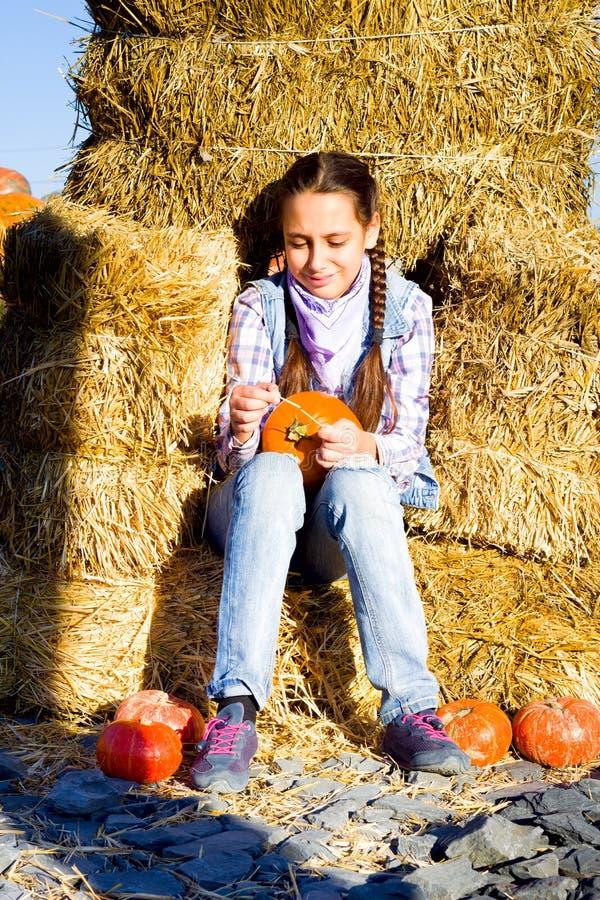 Młody nastolatek dziewczyny obsiadanie na słomie z pumkins na gospodarstwo rolne rynku Rodzinny odświętności dziękczynienie, Hall fotografia stock
