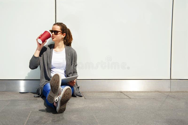 Młody nastolatek pije coffe i patrzeje na boku z pastylką nad biel ścianą zdjęcia stock