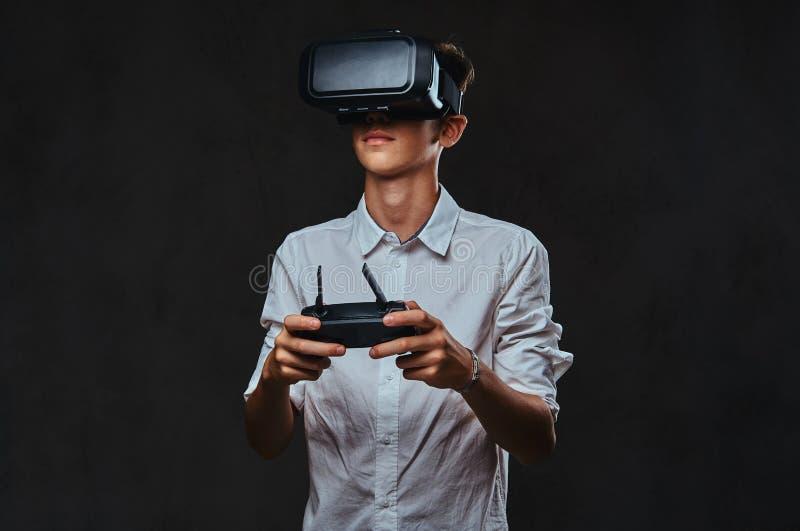 Młody nastolatek ubierający w białej koszula jest ubranym rzeczywistość wirtualna szkła i kontroluje quadcopter używać kontrola fotografia stock