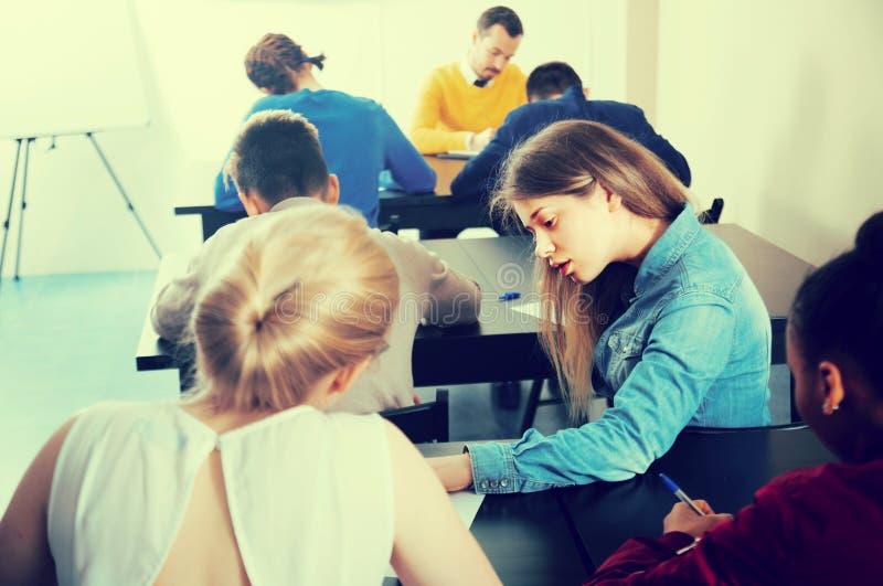 Młody nastolatka uczeń oszukiwa dalej i przyglądające test odpowiedzi zdjęcie stock
