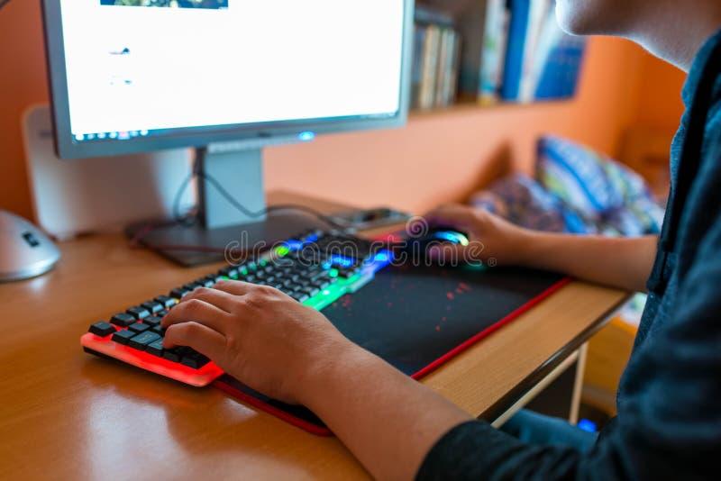 Młody nastoletni chłopak bawić się gra wideo na komputerze obraz stock