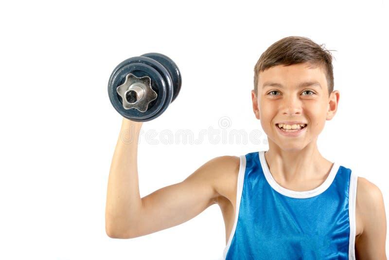 Młody nastoletni chłopak używa dumbbells fotografia royalty free