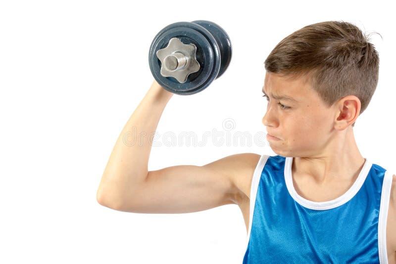 Młody nastoletni chłopak używa dumbbells zdjęcie royalty free
