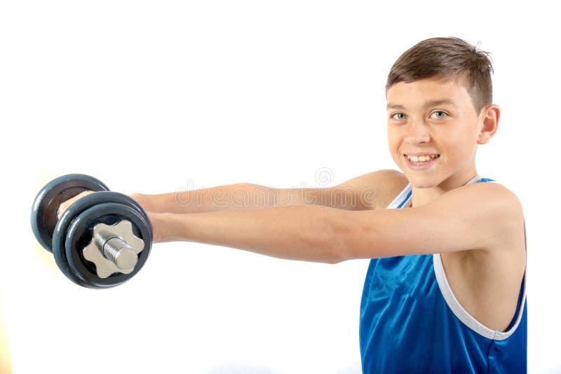 Młody nastoletni chłopak używa dumbbells zdjęcie stock