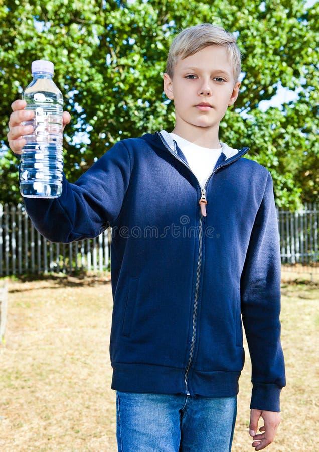 Młody nastoletni chłopak z butelką woda w parku zdjęcie royalty free