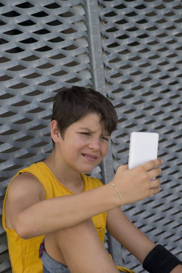 Młody nastoletni używać jego outdoors telefon zdjęcie stock