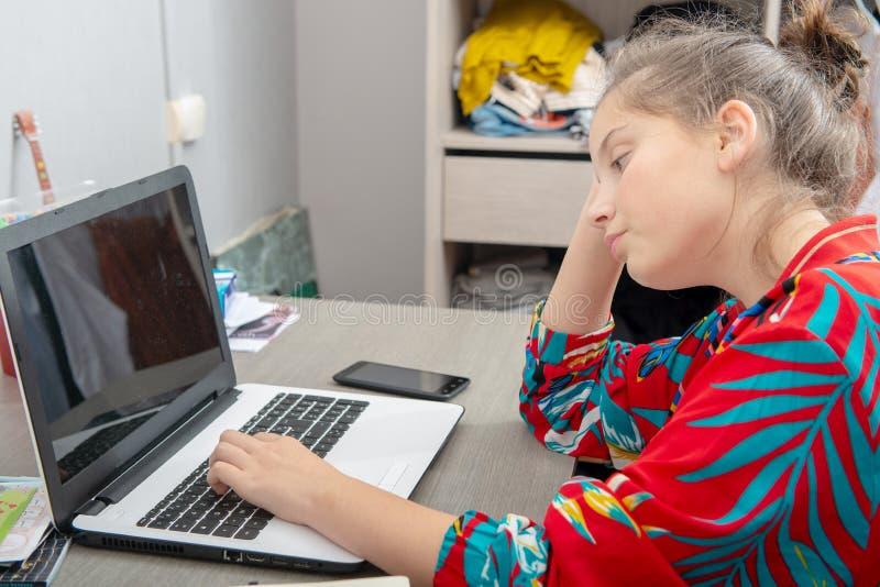 Młody nastoletniej dziewczyny obsiadanie przy biurkiem używać laptop fotografia royalty free