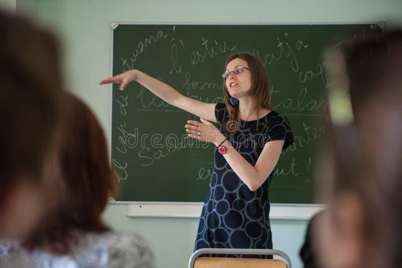 Młody nauczyciel przy uniwersytetem mówi uczni o fonetyce hiszpańszczyzny fotografia royalty free