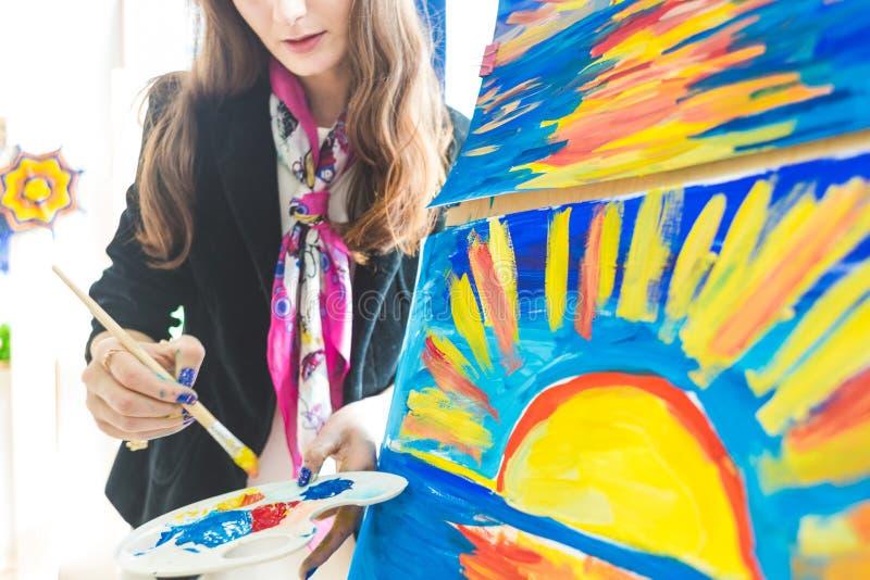 Młody nauczyciel w grupie preschool uczeń siedział rysunek obrazek Malujący na maelbert, palecie i farbach, Popiera zdjęcie stock