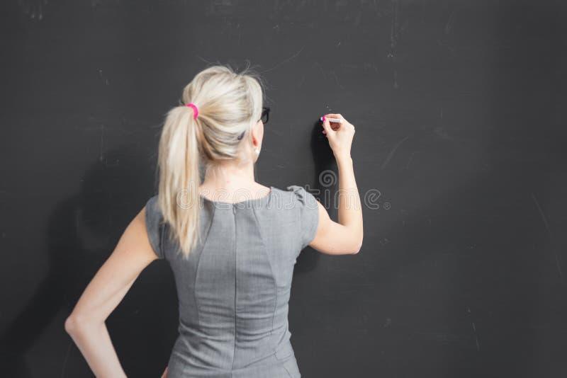 Młody nauczyciela writing z biel kredą na pustym blackboard w sala lekcyjnej zdjęcia royalty free