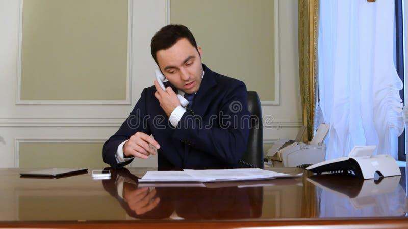 Młody niepełnosprawny biznesmen, saffered od Parkinson s choroby, siedzący w biurowym krześle, robić papierkowej robocie i odpowi zdjęcie stock