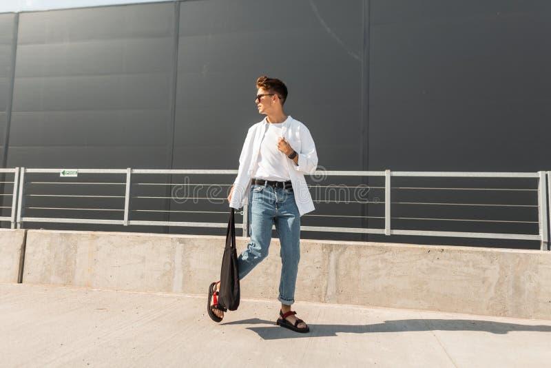Młody nowożytnego mężczyzny model w białej rocznik koszula w błękitnych eleganckich cajgach w okularach przeciwsłonecznych z czar obraz stock