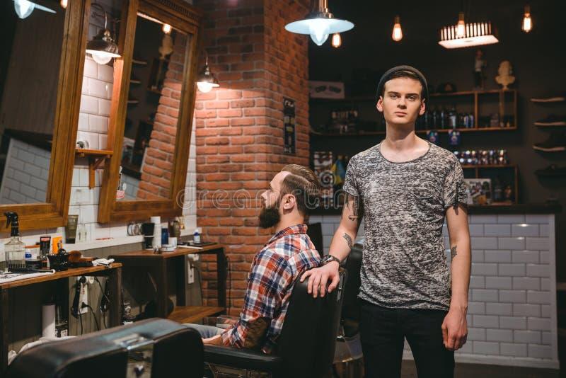 Młody nowożytny fryzjer męski na jego miejscu pracy z klientem zdjęcia royalty free