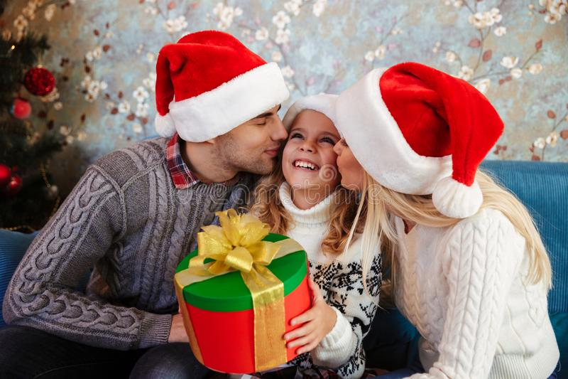 Młody ojciec i matka w Santa ` s kapeluszu całować tamte mały daug fotografia stock