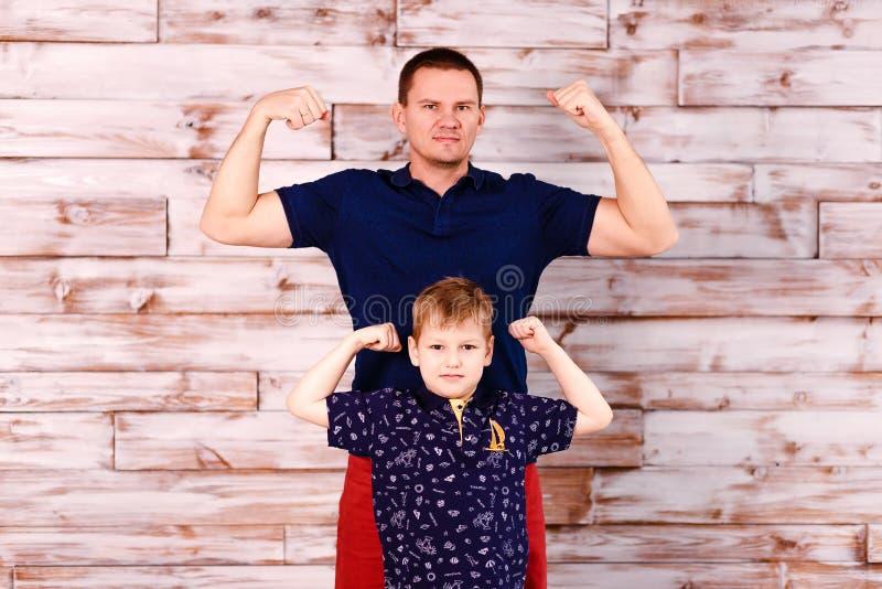 Młody ojciec i ośmioletni syn pokazujemy władzę mięśnie elegancki mężczyzna i chłopiec obraz stock