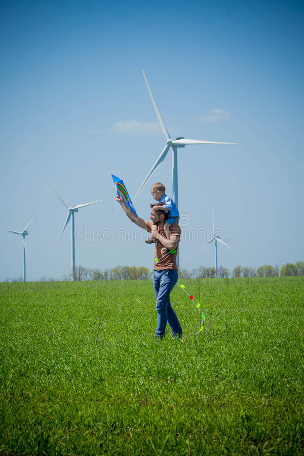 Młody ojciec niesie dziecka na jego ramionach i kani blisko wiatrowych generatorów zdjęcie stock