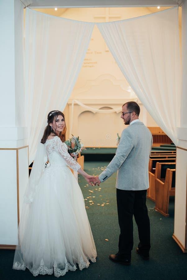 Młody państwo młodzi na ich dzień ślubu w kościelnym budynku zdjęcia stock