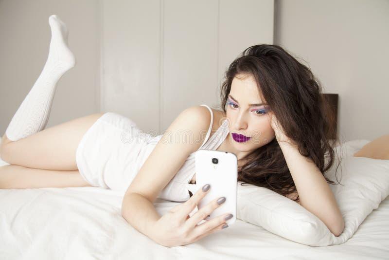 Młody piękna mienia smartphone zdjęcie stock