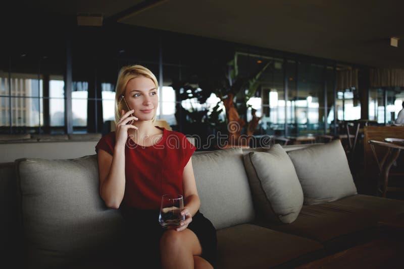 Młody piękny żeński przedsiębiorca opowiada na mobilnym mądrze telefonie podczas gdy siedzący z szkłem świeża woda w nowożytnej r zdjęcie royalty free