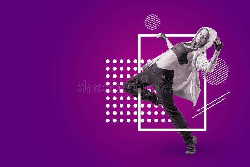 Młody piękny żeński tancerz w sleeveless uprawa wierzchołku, sweatpants i hoodie tanu na purpurowym tle z bielem, zdjęcia royalty free