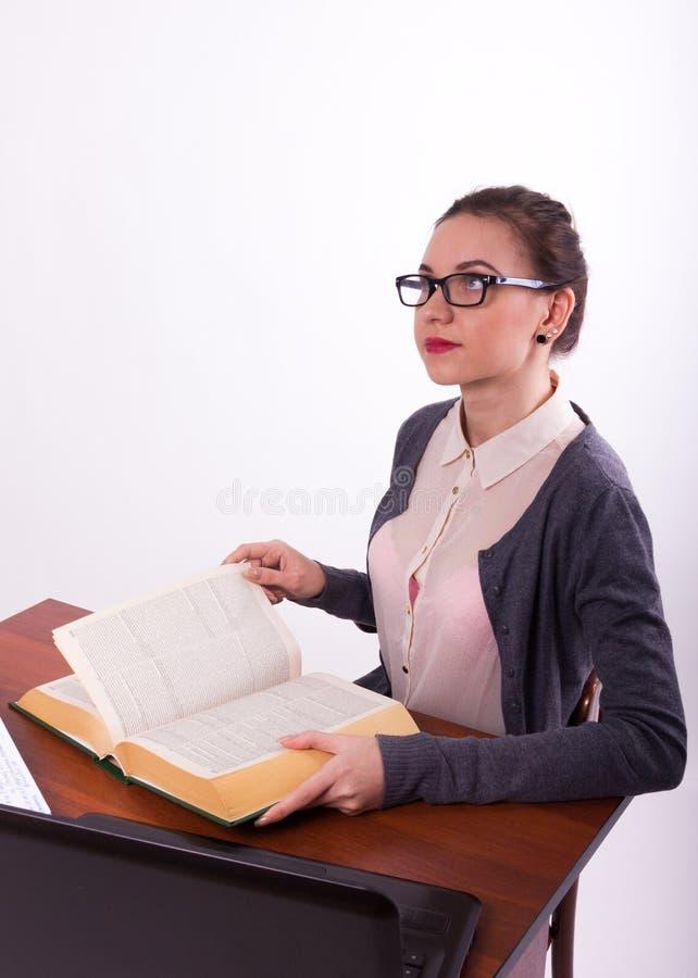 Młody piękny żeńskiego nauczyciela obsiadanie przy stołem obraz stock