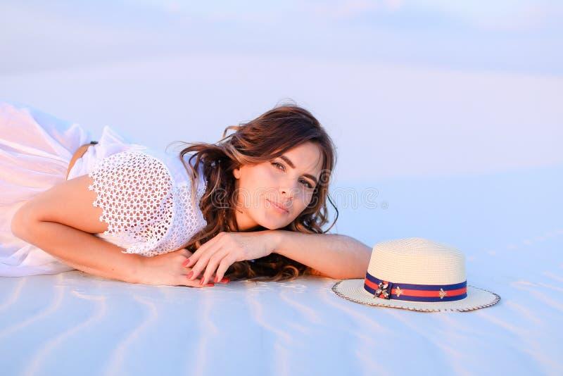 Młody piękny żeńskiej osoby lying on the beach na białym piasku blisko kapeluszu obraz stock