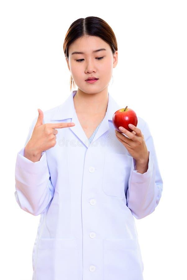Młody piękny Azjatycki kobiety lekarki mienie i wskazywać przy czerwienią a obrazy stock