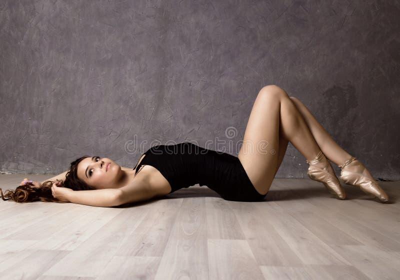 Młody piękny baletniczy tancerz w pointe butach, tanczy w szarym tle obraz stock
