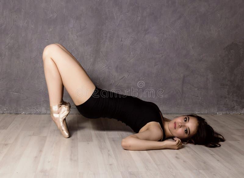 Młody piękny baletniczy tancerz w pointe butach, tanczy w szarym tle obrazy royalty free