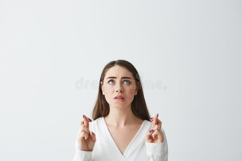 Młody piękny bizneswomanu modlenie gryźć wargę przyglądającą up nad białym tłem obraz stock