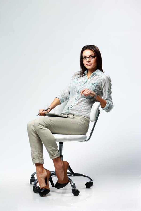 Młody piękny bizneswomanu obsiadanie na biurowym krześle zdjęcia stock