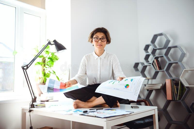 Młody piękny bizneswomanu obsiadanie na stole przy miejscem pracy w biurze obrazy stock