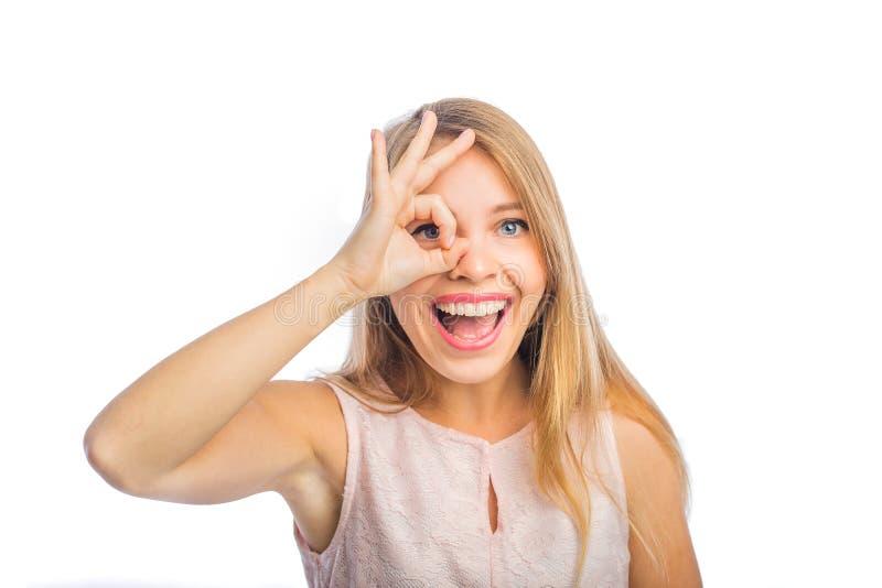 Młody piękny blondynki kobiety przedstawień ok blisko ona oczy entuzjastycznie i uśmiechy z jej usta otwartym, w górę strzału dal zdjęcie stock