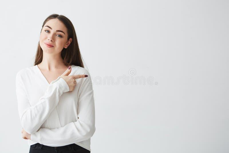 Młody piękny brunetka bizneswoman ono uśmiecha się patrzejący kamerę wskazuje palec w stronie nad białym tłem zdjęcie stock