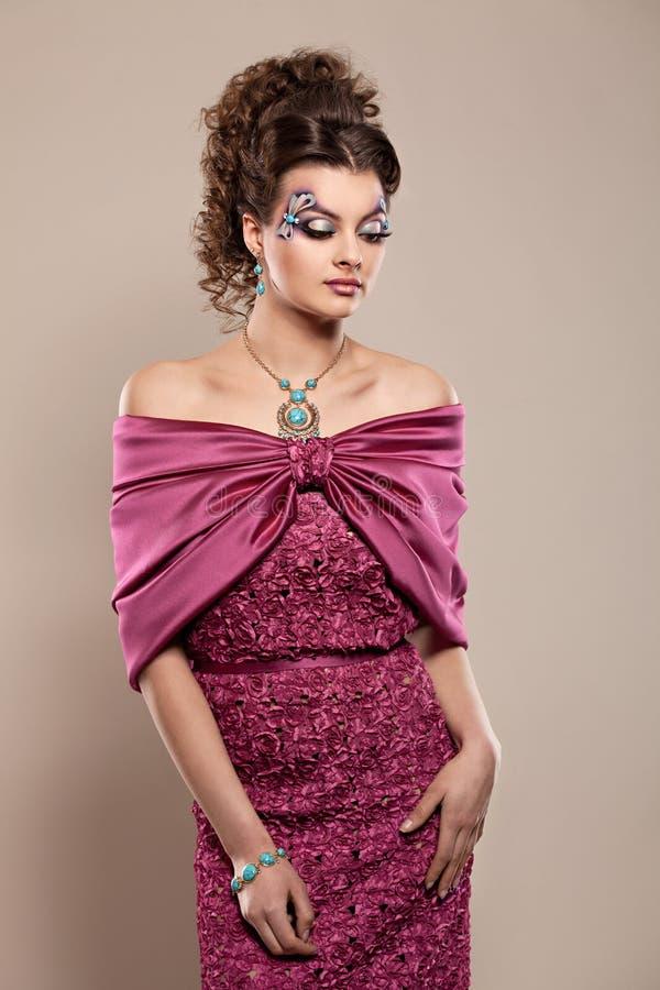 Młody piękny brunetka model w wspaniałym smokingowym Burgundy kolorze zdjęcia royalty free