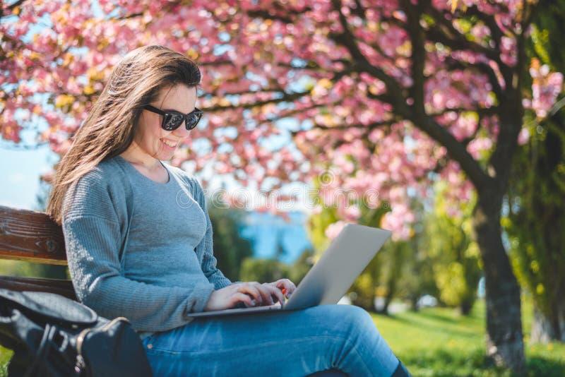 Młody piękny brunetka uczeń siedzi na banch z laptopem zdjęcia royalty free