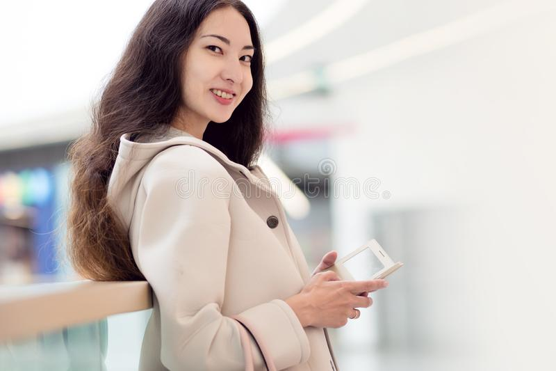 Młody piękny dziewczyna azjata, uses telefon komórkowy, tło, zakupy centrum handlowe lub centrum biznesu, obrazy stock