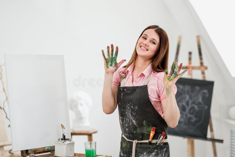 Młody piękny dziewczyna malarz w białym studiu z brudną palm przedstawień klasą, śmia się i raduje się fotografia stock