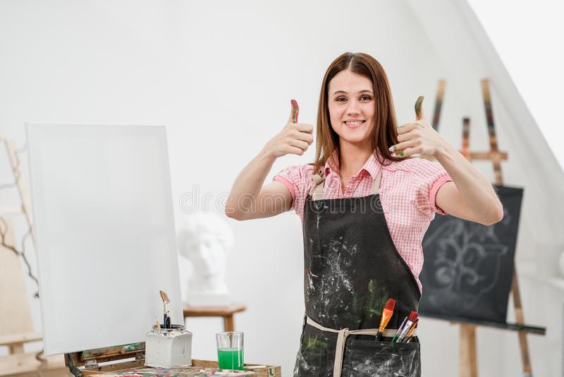 Młody piękny dziewczyna malarz w białym studiu z brudną palm przedstawień klasą, śmia się i raduje się zdjęcia royalty free