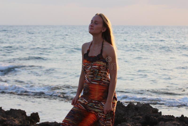 Młody piękny dziewczyna stojak na plaży i trzyma ona heeled sandały fotografia royalty free