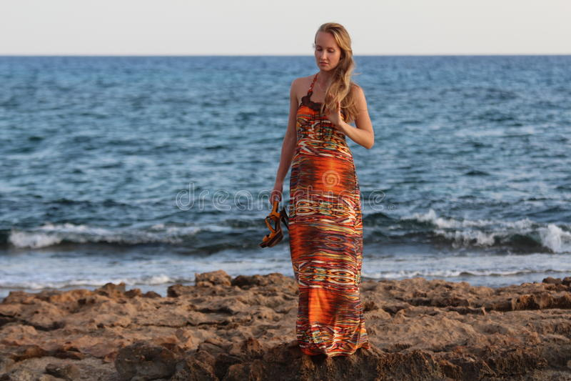 Młody piękny dziewczyna stojak na plaży i trzyma ona heeled sandały obrazy royalty free
