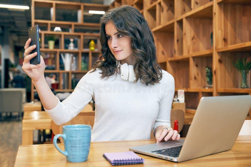 Młody piękny dziewczyny blogger uczeń z długim kędzierzawym włosy w białym pulowerze z hełmofonami na szyi i robi selfie obraz royalty free