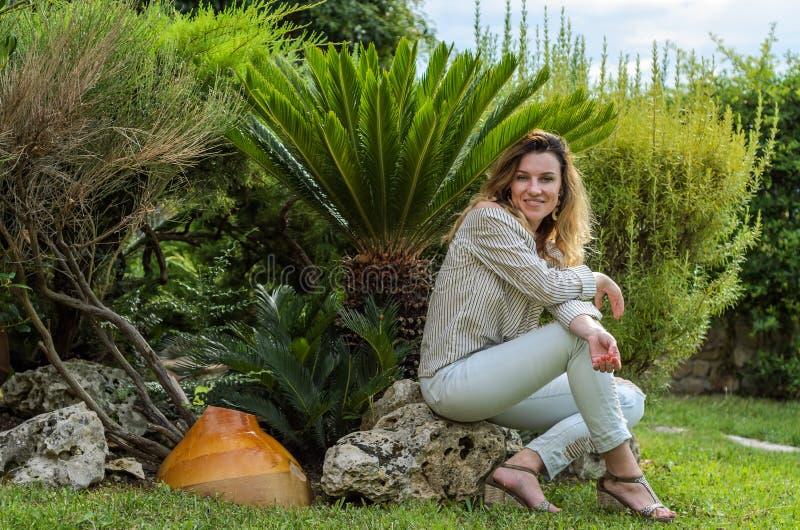 Młody piękny dziewczyny obsiadanie na kamieniu blisko tropikalnego drzewka palmowego zdjęcia stock