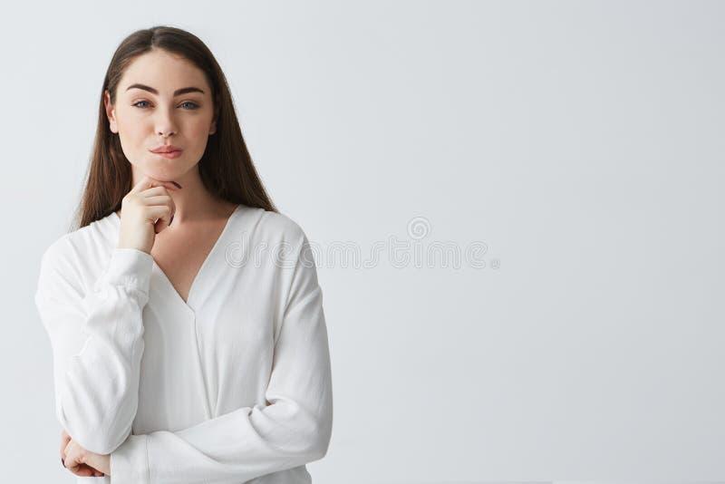 Młody piękny figlarnie bizneswoman ono uśmiecha się z chytrym chytrym spojrzeniem patrzejący kamerę nad białym tłem fotografia stock
