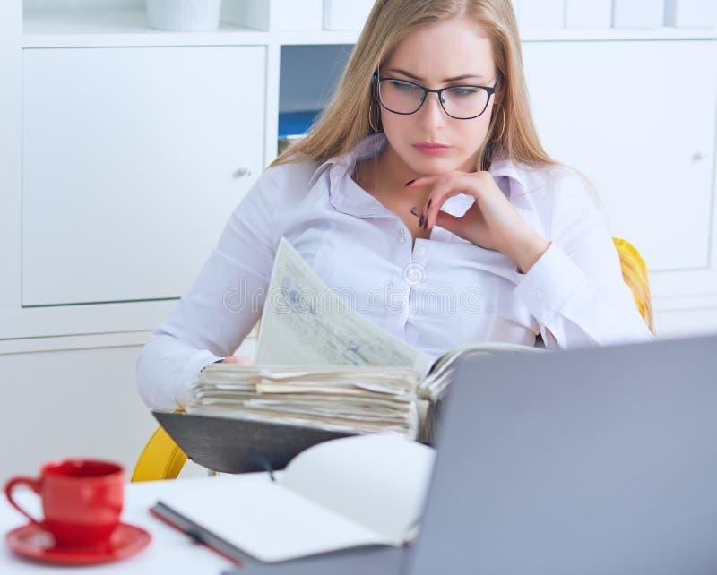 Młody piękny Kaukaski bizneswoman w szkła działaniu na notebooku i biznesowy dokument przy biurem obraz royalty free