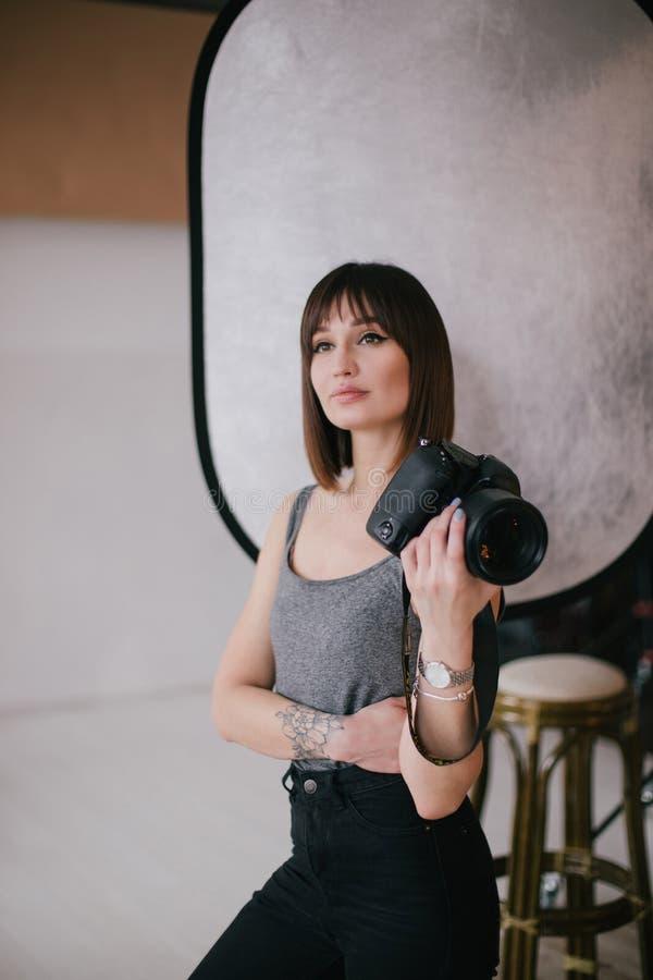 Młody piękny kobieta fotograf z fachową fotografii kamerą w studiu zdjęcie stock