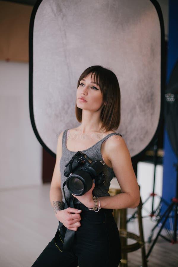 Młody piękny kobieta fotograf z fachową fotografii kamerą w studiu obrazy royalty free