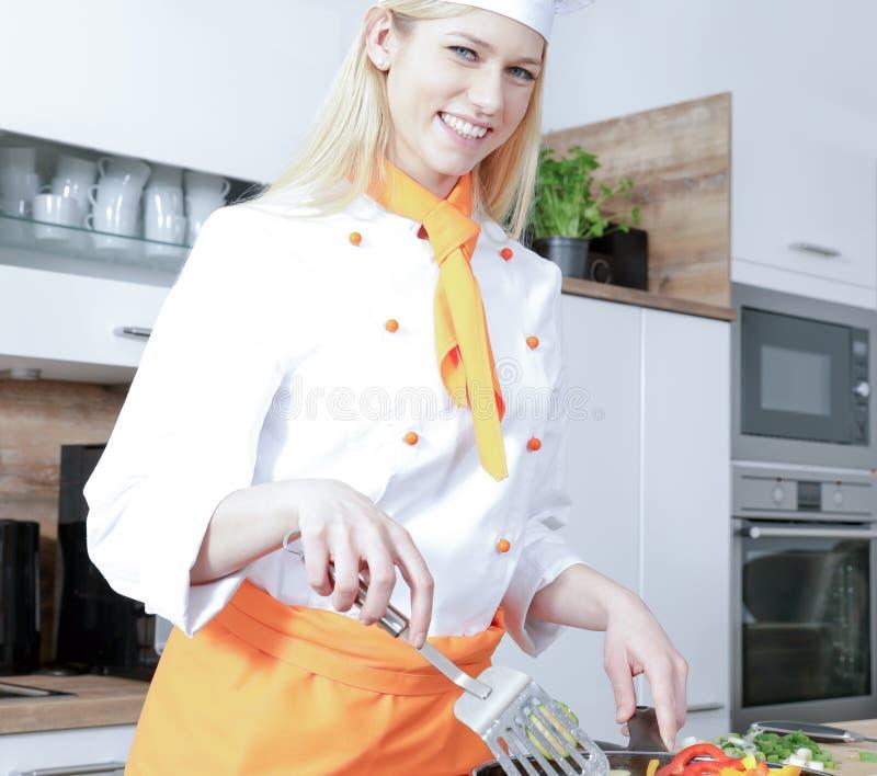 Młody piękny kobieta kucharz gotuje w kuchni niektóre jedzenie z warzywami mięsnymi zdjęcie stock
