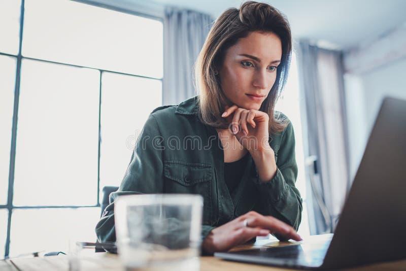 M?ody pi?kny kobieta modela obsiadanie przy wygodnym u?ywa? laptopem i kar?em Pracuj?cy proces przy coworking zdjęcia stock