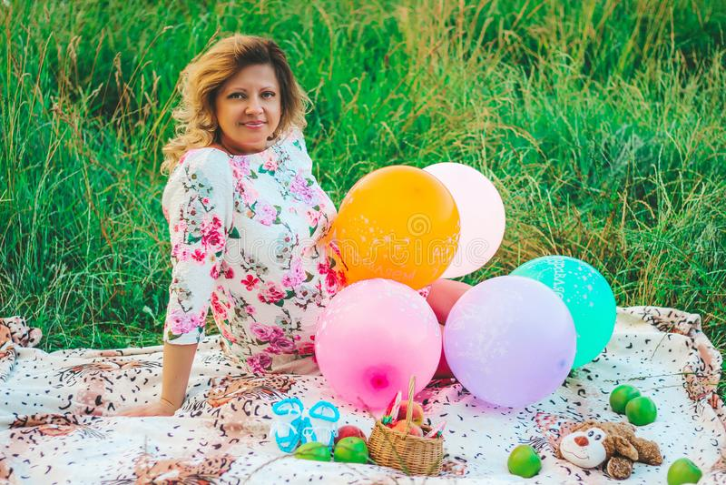 Młody piękny kobieta w ciąży obsiadanie przy pinkinem na koc w parku z kolorowymi balonami w ręki zbliżeniu zdjęcie royalty free